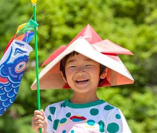 a kid putting on paper craft samurai helmet