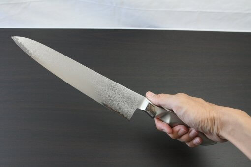 Japanese Chef Knife, Damascus Gyuto size LL, grabbed by a man's hand