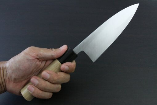 Japanese professional chef knife, left-handed Deba fillet knife, steel 150mm, grabbed by a man's hand