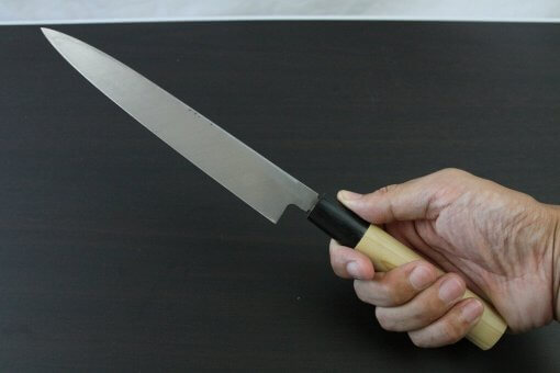 Japanese professional chef knife, Yanagiba Sushi knife, 1st grade 210mm, grabbed by a man's hand