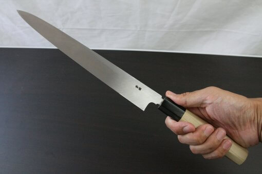 Japanese professional chef knife, Yanagiba sushi knife, steel 270mm, grabbed by a man's hand