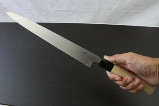 Japanese professional chef knife, Yanagiba sushi knife, steel 300mm, grabbed by a man's hand