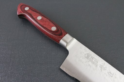 Toshu Santoku multi-purpose Japanese chef's knife, hammered finish blade and red handle, diagonal front view
