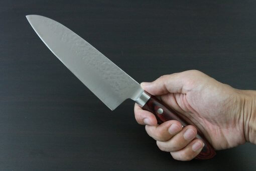 Toshu Santoku multi-purpose Japanese chef's knife, hammered finish blade and red handle, grabbed by a man's hand