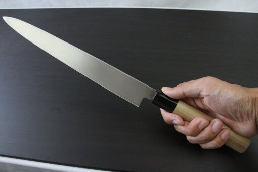 Japanese professional chef knife, Yanagiba Sushi knife, stainless steel 270mm, grabbed by a man's hand