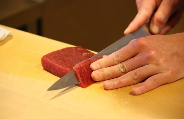cut tuna by a Japanese sushi knife