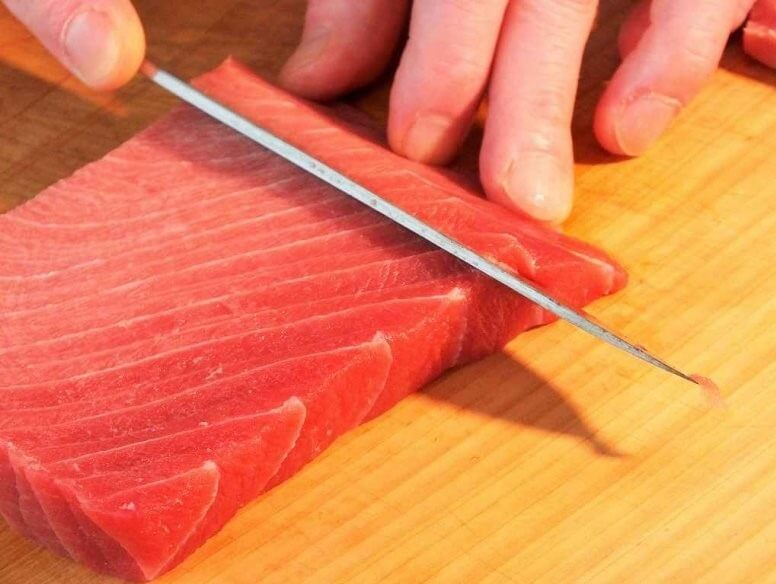 cut tuna sashimi by a sushi knife