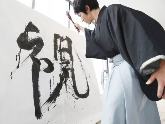 a calligrapher writing his art on large paper