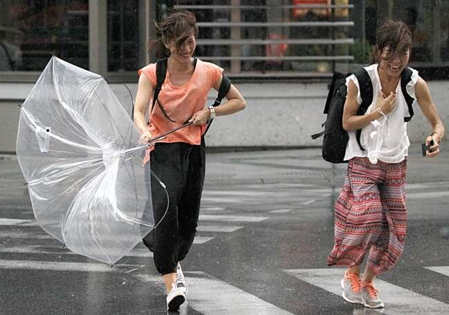 women blew by wind of typhoon across a street